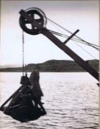 "1938 – A man on hoist off the dredger ""Sand Chime""."