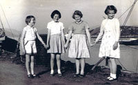 1960 ish - Down the Pier, in front of the White Heather Hotel from left to right:  Jane Forsyth, Janette MacPherson, Caroline Soper, Ann Robertson with Big Finlay on the bow of the Sweet Home in the background